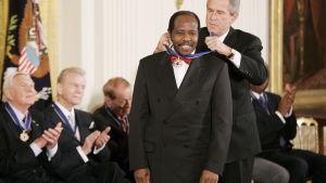 President George W. Bush fäster en medalj på den rwandska hotellägaren Paul Rusesabagina som räddade över 1 200 människor under inbördeskriget 1994