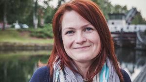 Punahiuksinen nainen jolla tummansininen villatakki ja kukallinen huivi kaulassa hymyilee kohti kameraa. Taustalla vettä.