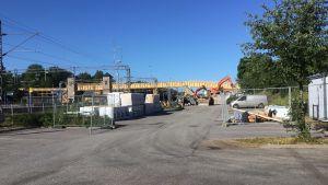En asfaltsplan där det pågår byggarbeten. En bakgrunden en bro av trä.