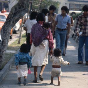Meksikolaisia kävelemässä kadulla, äiti taluttaa kahta pientä lasta.