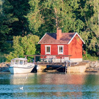 en röd stuga vid vattnet med en båt förtöjd vid en liten brygga. Mycket skog bakom.