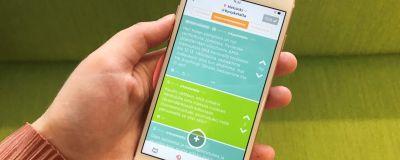 En hand håller i en telefon där Jodel-appen syns.