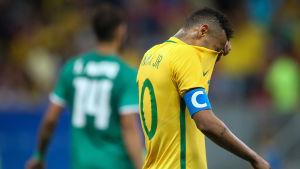Brasiliens Neymar döljer ansiktet under tröjan.