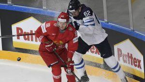 Osala och en vitrysk spelare kämpar om pucken.