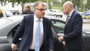 Statsminister Juha Sipilä stiger ut ur en bil med två säkerhetsvakter i bakgrunden.