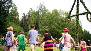 Ihmisiä tanssimassa juhannussalkon ympärillä