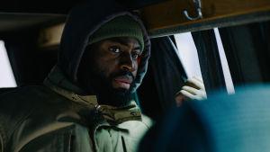 Francis i baksätet på en bil som kör genom natten.
