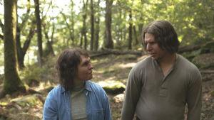 Tina (Eva Melander) och Vore (Eero Milonoff) går bredvid varandra i skogen och ser på varandra.