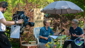 En kvinnlig reporter intervjuar en man för TV.