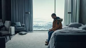 Mies istuu hotellin sängyn laidalla katsoen maahan, taustalla ikkunan takana luminen maisema.