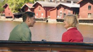 Två personer sitter vid ån och ser på varandra, i bakgrunden Borgås röda gammaldags byggnader.