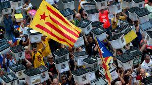 Demonstranter i Barcelona bär valurnor som användes vid folkomröstningen för ett år sedan
