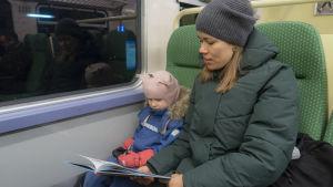 Äiti lukee lapselle kirjaa junassa