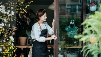 Kvinna i förkläde står och håller i en dörr till en blombutik. Runt dörren finns växter och den pryds av en liten ekorrformad skylt där det står att det är öppet.