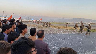 Folk står bakom taggtråd medan amerikanska soldater håller vakt på flygplatsen i Kabul.