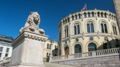 Leijonapatsas jalustalla parlamenttitalon edessä. Norjan lippu liehuu talon katolla.