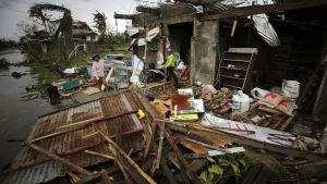 Ett filippinskt par inspekterar sitt hem som förstörts av tyfonen Mangkhut.