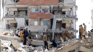 Räddningsarbetare och offer letar efter överlevande och ägodelar i ett raserat hus i Sarpol-e-Zahab.