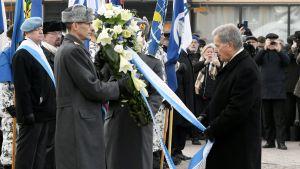 Sauli Niinistö håller i en blåvit banderoll som är fäst vid en blomkrans, omringad av människor, på Kaserntorget i Helsingfors.