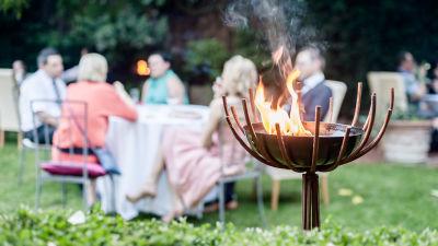 En trädgårdsfest med långbord och mänskor i stolar. En eld/brasa brinner i förgrunden.