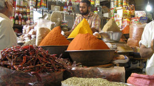 A vendor sells grains and spices at his shop in Karachi Pakistan.