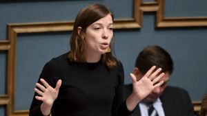 Li Andersson gestikulerar med händerna i riksdagens talarbås.