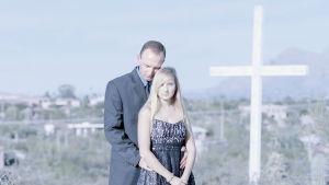 En bild på en far och en dotter och ett kors.