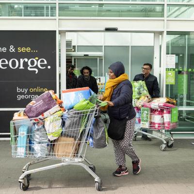 Nainen ja mies työntävät täyteen lastattuja ostoskärryjä kaupan ovella.