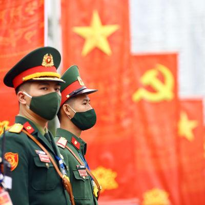 Soldater i förgrunden. I bakgrunden Vietnams och kommunistpartiets flaggor.