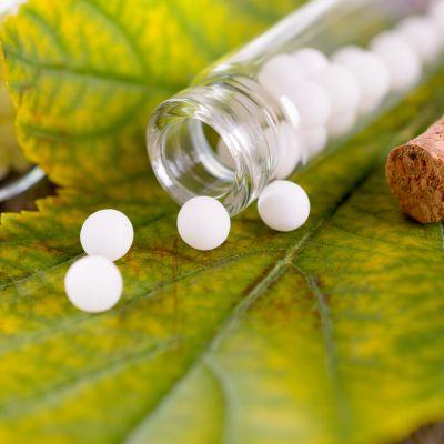 Valkoisia pillereitä ja lasipurkki vihreän lehden päällä