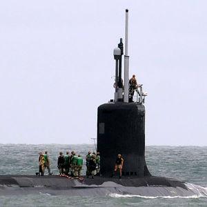 En stor ubåt som delvis sticker upp ovanför vattenytan. På ubåten står ett tiotal personer.