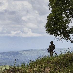 En soldat står på en grön sluttning och tittar ut över staden Beni.