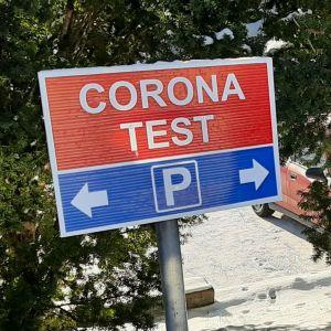En rödblå skylt i snön meddelar att man får parkera här då man kommer för coronatest.