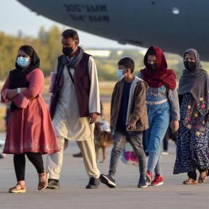 Afghanska flyktingar på väg ut ur ett flygplan.