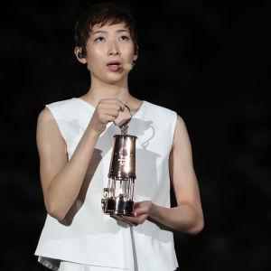 Rikako Ikee håller upp en trofé i samband med OS-festlighet.