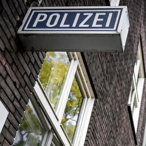 Mörk tegelbyggnad med en skylt med texten polizei, som betyder polis på tyska. Det här är polisstationen i Muelheim an der Ruhr.