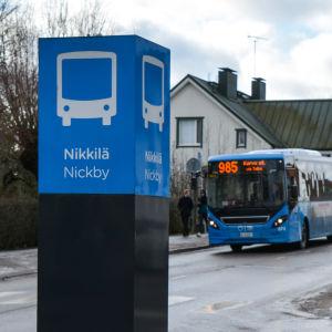 En blå stadsbuss kommer körande mot en busstation i Nickby centrum.