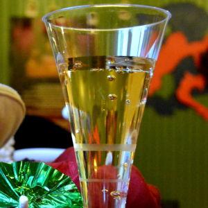 ett glas med bubblig dryck och en massa huvudbonader på varandra i olika färger och ett litet glassparaply i grönt