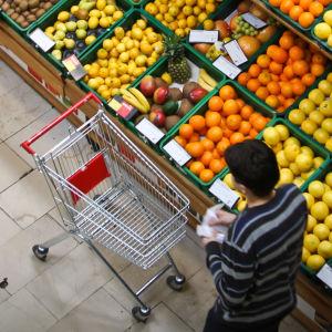 Folk handlar vid fruktavdelningen i en matbutik.