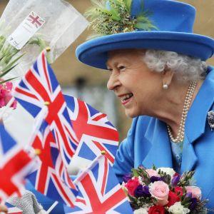 Drottning Elisabeth i ett publikhav av brittiska flaggor och blommor..