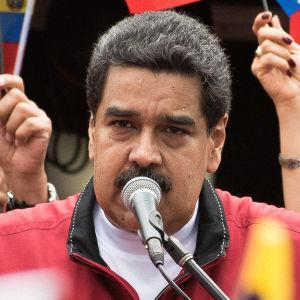 Venezuelas president Nicolas Maduro håller tal. Han är omgiven av landets flaggor.