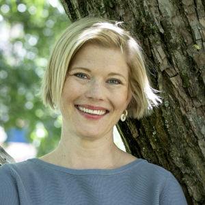Kvinna poserar framför träd