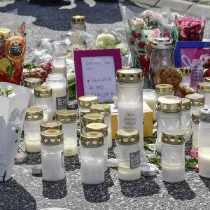 Flickor kramar och tröstar varandra framför ljus och blommor som förts till bensinstationen där en 12-årig flicka blev skjuten.