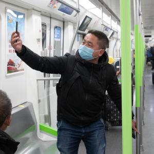 Passagerare i ett tunnelbanetåg i Wuhan, Kina. En av passagerarna tar en selfie. Bilden är tagen den 28 mars, samma dag som tunnelbanan öppnade igen efter paus på grund av coronavirusutbrottet i staden.