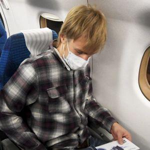 En person på ett Finnairplan i ett flygsäte. Killen är iklädd i munskydd.