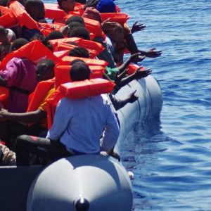 Räddningsarbetare kastar vattenflaskor till flyktingar på en gummibåt på Medelhavet.