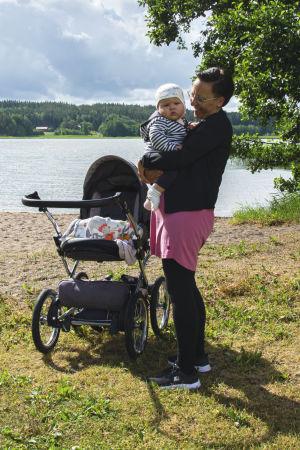 Nina Bäckström bär Ken Bäckström i sin famn på en strand.