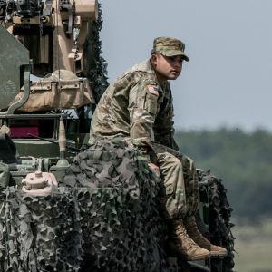 En amerikansk soldat sitter på ett pansarfordon