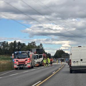 Räddningspersonal och räddningsfordon står vid en väg där det skett en olycka. Bilar väntar i kö.