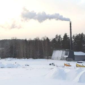 Ett värmeverk i vintrig miljö där det kommer ut rök ur skorstenen.